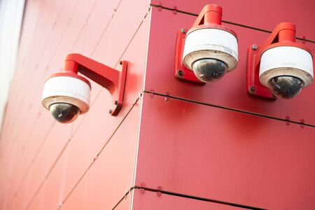 Three red-white surveillance cameras on red metal wall. Photo with depth of field