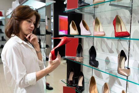A girl pondered chooses a red boat shoes in high heels in a mall.