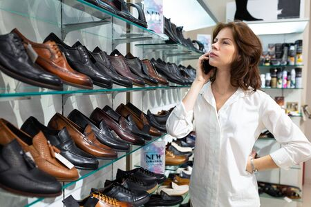 Young woman calls and advises about buying men s shoes.