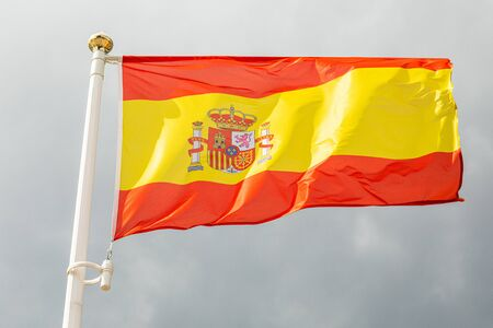 Spanish flag on a flagstuff in front of the sky
