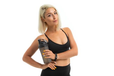 A sports woman with blonde hair and bright manicure holds a sports water bottle.