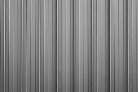 Front view of gray ribbed metal surface on fence or wall for backdrop.