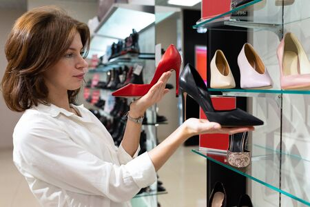 A young female pondered chooses between red and black boat shoes in high heels.