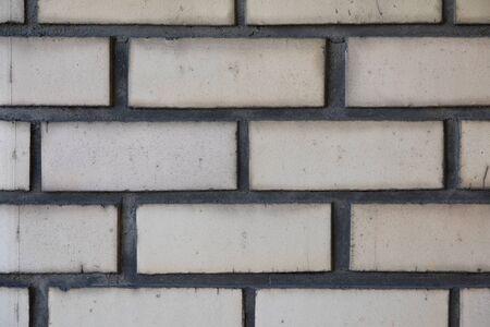White brick wall with dark beton. Close-up image Imagens