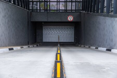 Entrance to underground car parking with roller-shutter door and road dividers