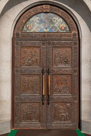 Wooden arched door of church with carving of the scenes from Bible and tinted glass