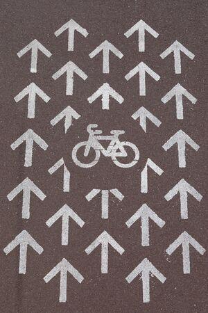 Road marking Bike path surrounded with arrows pointing traffic direction allowed on dark grey asphalt Reklamní fotografie