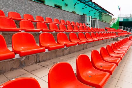 New orange plastic seat places for sports spectators.