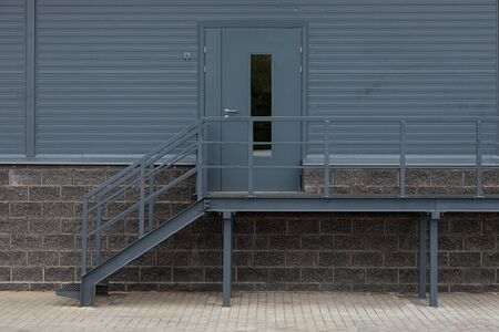 Dark grey metal back door with steps and railing Stock Photo