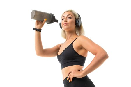A sports woman with blonde hair and bright manicure in headphones, black sports topics and leggings holds a sports water bottle. Banco de Imagens