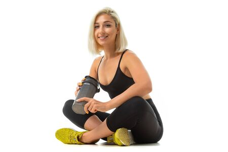 A sports girl with blonde hair and bright manicure in headphones, black sports topics, leggings and yellow sneaker holds a sports water bottle.