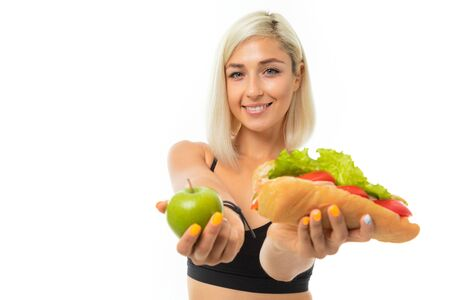 A young sports girl with blonde hair in a black sports top and black leggings holds a green apple and sandwich. 스톡 콘텐츠