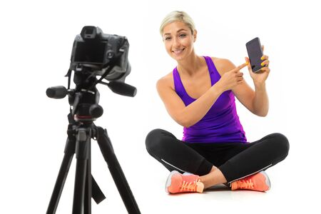 The young sporty girl with a fair hair in a black sports topic, black leggings and bright sneakers sits in front of the camera shows phone. 스톡 콘텐츠