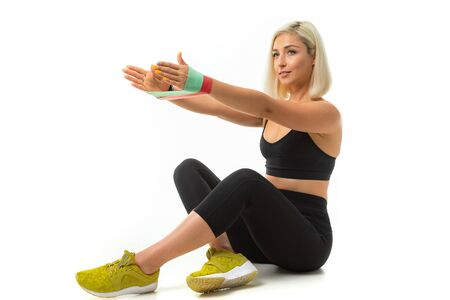 A young sports girl with blonde hair and bright manicure in black sports topics, leggings and sneakers does exercises with sports rubber.