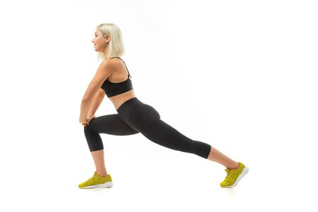 A young sports girl with blonde hair and bright manicure in black sports topics, leggings and sneakers does exercises.