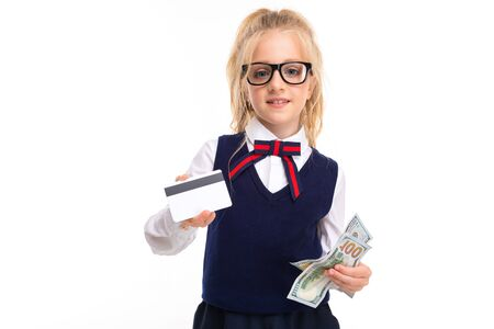 A little girl with blonde hair stuffed in a horse tail, large blue eyes and a cute face in square black glasses with a pass and dollars.