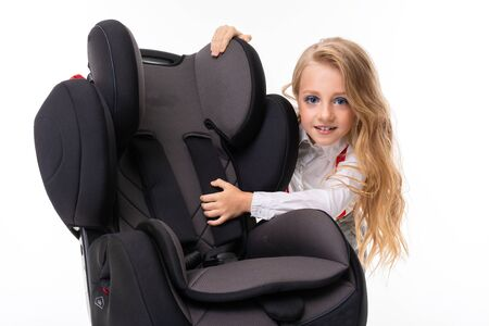 A little girl with makeup and blonde hair in a white shirt, red pull-ups, pants in a cage, red socks and shoes with a baby chair. Stockfoto