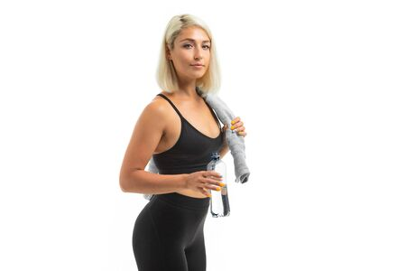 A young sports girl with blonde hair in a sports axe and black leggings holds a blue towel and a bottle of water.