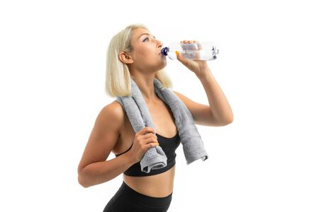 A young sports girl with blonde hair in a sports axe and black leggings holds a blue towel and a drinks a water.