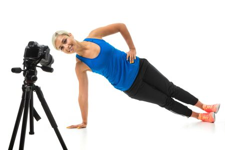 The young sporty girl with a fair hair in a black sports topic, black leggings and bright sneakers carries out exercises in front of the camera. 스톡 콘텐츠