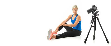 The young sporty girl with a fair hair in a black sports topic, black leggings and bright sneakers does an extension of muscles in front of the camera. Stockfoto