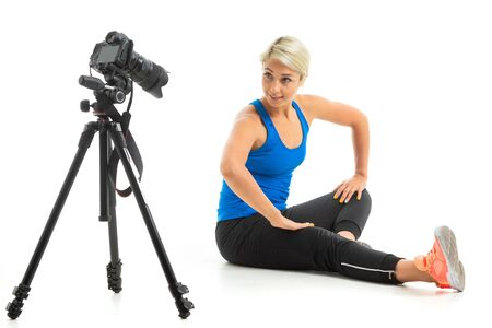 The young sporty girl with a fair hair in a black sports topic, black leggings and bright sneakers does an extension of muscles in front of the camera. Banco de Imagens