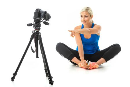 The young sporty girl with a fair hair in a black sports topic, black leggings and bright sneakers does an extension of muscles in front of the camera. 스톡 콘텐츠