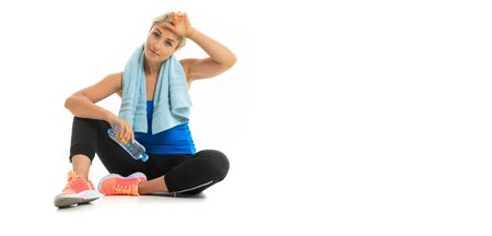 A young sports girl with blonde hair in a black sports axe, black leggings and bright sneakers with a towel around her neck tired after training.