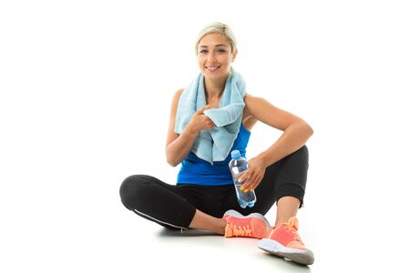 A young sports girl with blonde hair in a black sports axe, black leggings and bright sneakers with a towel around her neck and a bottle of water tired after training. 스톡 콘텐츠