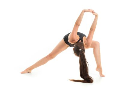 A beautiful young woman gymnast with dark long hair does warm-up, stretch her muscles and jumping.