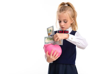 A little girl with blond hair stuffed in a horse tail, large blue eyes and a cute face folds dollars into a moneybox.