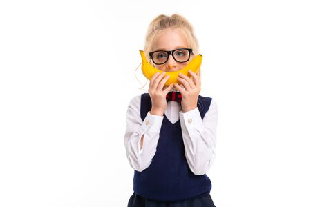 A little girl with blonde hair stuffed in a horse tail, large blue eyes and a cute face in square black glasses fools with a banana.