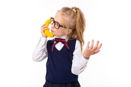 A little girl with blonde hair stuffed in a horse tail, large blue eyes and a cute face in square black glasses talks on a banana.