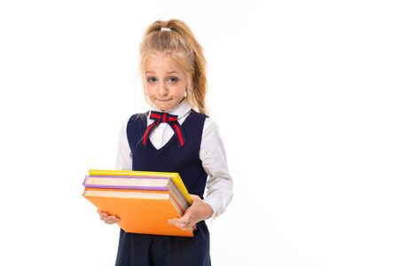 A little girl with blonde hair stuffed in a horse tail, large blue eyes and a cute face carries heavy books.