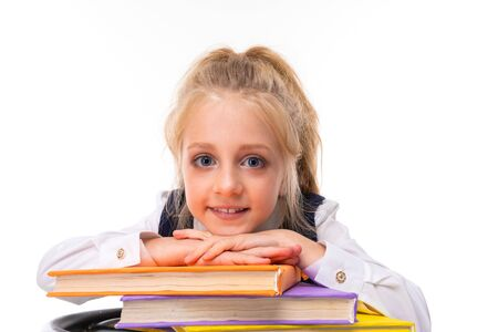 A little girl with blonde hair stuffed in a horse tail, large blue eyes and a cute face with books.