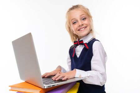 A little girl with blonde hair stuffed in a horse tail, large blue eyes and a cute face with a laptop on the books.