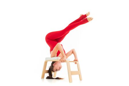 A beautiful young woman gymnast with dark long hair stuffed in a horse tail in a red sports elastic suit performs a peeling scissor standing on her hands Stockfoto