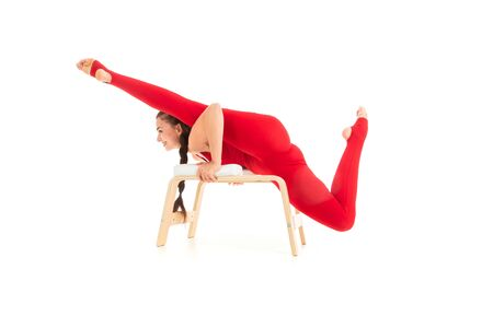 A beautiful young woman gymnast with dark long hair stuffed in a horse tail in a red sports elastic suit sits on a twine