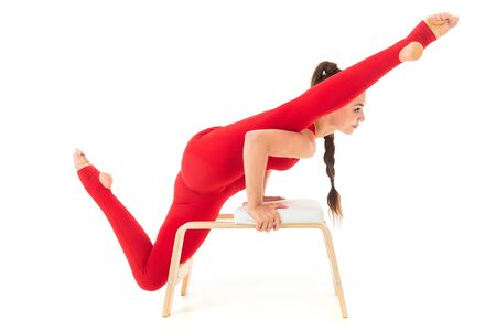 A beautiful young woman gymnast with dark long hair stuffed in a horse tail in a red sports elastic suit sits on a twine and stands on a hands.