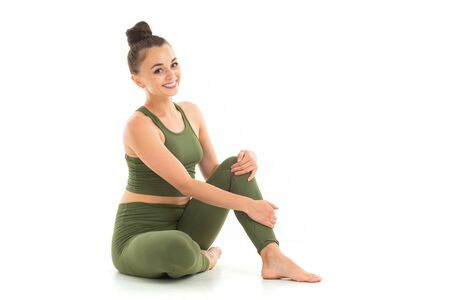 A beautiful young female gymnast with dark long hair stuffed into a bundle in a green sports elastic suit sits.