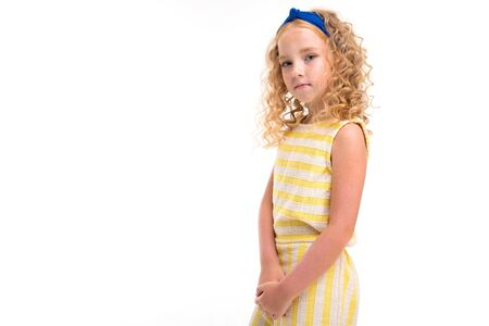 A little girl with red heap hair in a white and yellow striped summer suit, with a blue bandage on her head stands.