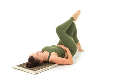 A beautiful young woman gymnast with dark long hair stuffed in a bundle in a green sports elastic suit lies and meditates.
