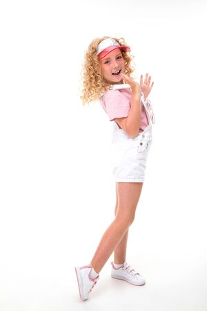 Little girl with red heap hair in shirt, white jumpsuit and wearing white sneakers and cap.