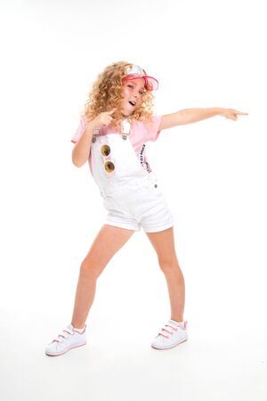 A little girl with red heap hair in a shirt, white jumpsuit, white sneakers, cap and round sun glasses dances.