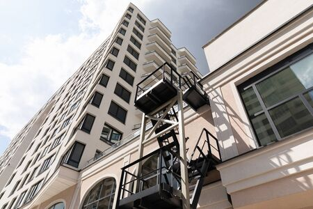 Modern high apartment building of increased comfort bottom view. The walls of the building are faced with beige plaster with wide windows and metal fire-escape, diagonal view Stockfoto