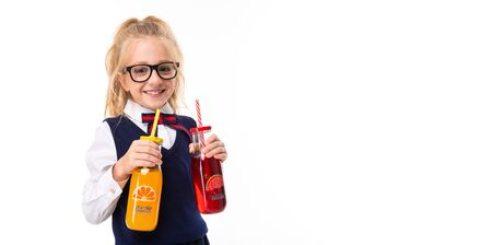 A little girl with blond hair stuffed in a horse tail, large blue eyes and a cute face in square black glasses keeps orange and watermelon juice in a glass bottle.