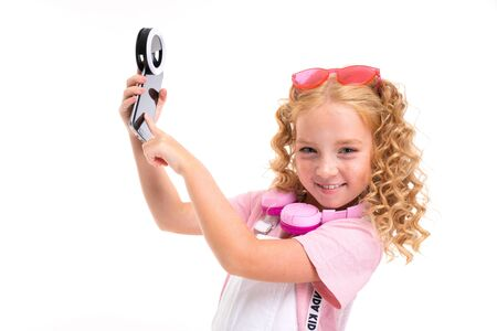 A little girl with red heap hair in a shirt, white jumpsuit, white sneakers, pink headphones and glasses holds her phone.