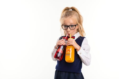 A little girl with blond hair stuffed in a horse tail, large blue eyes and a cute face in square black glasses drinks orange and watermelon juice in a glass bottle of tube.