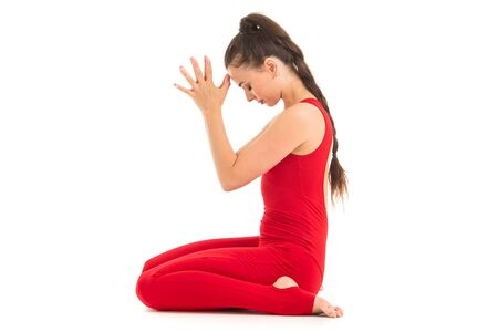 A beautiful young woman gymnast with dark long hair stuffed in a horse tail in a red sports elastic suit meditates.