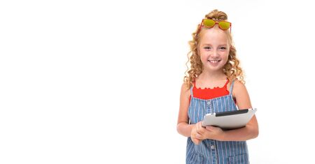 A little girl with red heap hair in a red jersey and blue-and-white jumpsuit in a stripe holds a tablet. and smiling.